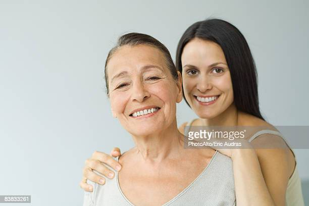 woman behind senior mother, hands on shoulders, both smiling at camera, portrait - hand auf der schulter stock-fotos und bilder