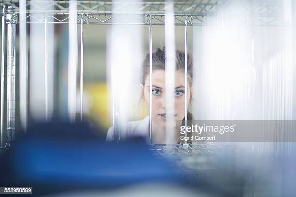 woman behind shelves of jeans in laundry - sigrid gombert stock pictures, royalty-free photos & images