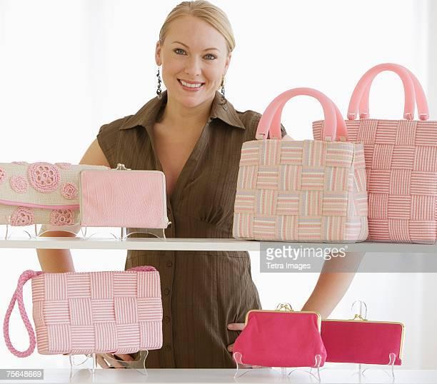 Woman behind shelves of purses
