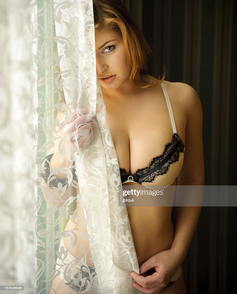 Woman behind the curtain : Stock Photo