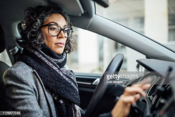 woman behind the wheel using phone for navigation - driver stock pictures, royalty-free photos & images