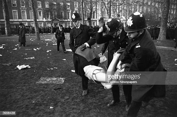 A woman being carried off by three policemen during an antiVietnam war demonstration in London