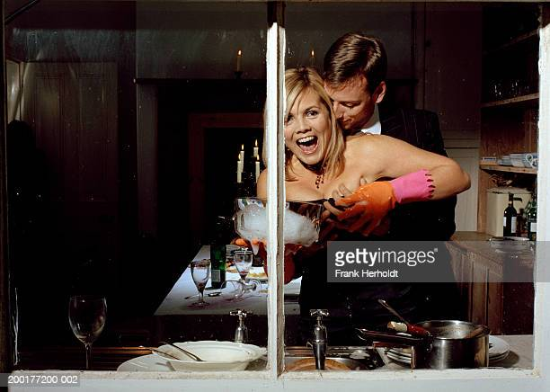 woman being grabbed by man whilst washing dishes, view through window - chest kissing stock pictures, royalty-free photos & images