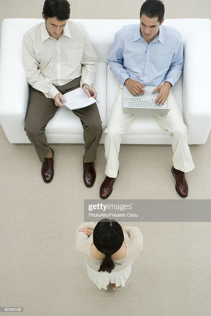 Woman being interviewed by two men, one man holding laptop, high angle view : Stock Photo