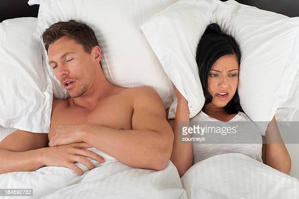Woman being kept awake by snoring