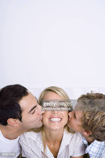 woman being kissed on cheeks by husband and son, smiling, portrait - cheek stock pictures, royalty-free photos & images