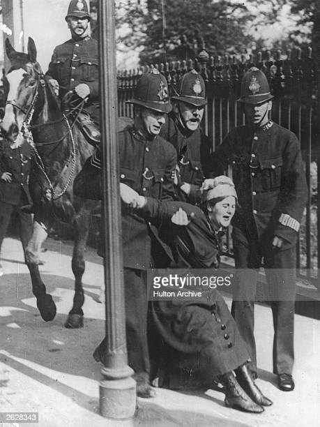 A woman being restrained by three policemen during the suffragette disturbances outside Buckingham Palace London
