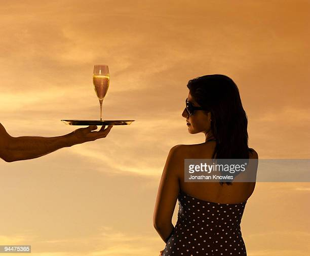woman being served champagne - wealth stock pictures, royalty-free photos & images