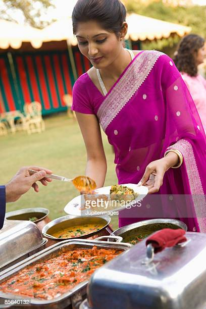 woman being served in buffet line - sari stock pictures, royalty-free photos & images