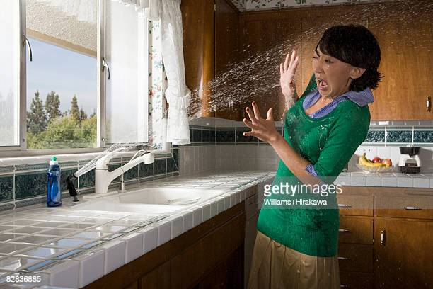 Woman being sprayed by water from kitchen sink