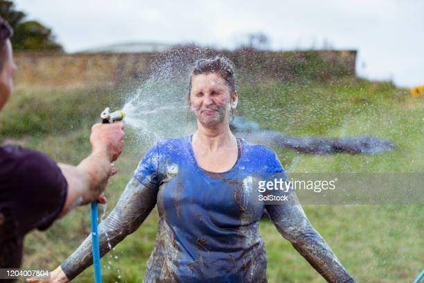 woman being sprayed clean after charity event - hose stock pictures, royalty-free photos & images