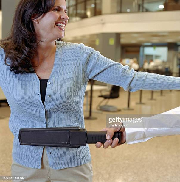woman being swiped by metal detector at airport security checkpoint - security check - fotografias e filmes do acervo
