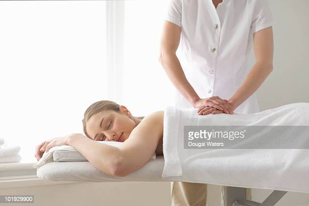 woman being treated by masseuse. - massage stock pictures, royalty-free photos & images