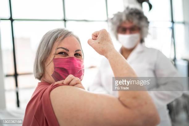 vrouw die wordt gevaccineerd en bicepsspier buigt - die gezichtsmasker draagt - human arm stockfoto's en -beelden