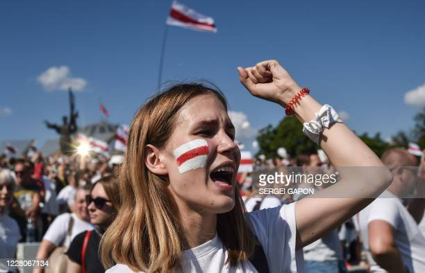 TOPSHOT A woman Belarus opposition supporter with a drawing of a former whiteredwhite flag of Belarus used in opposition to the government punches...