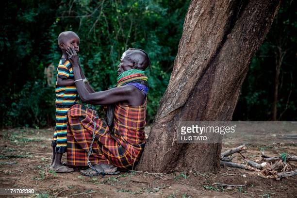 A woman belonging to the Turkana community removes dirt from her son's face while sitting next to her village in Morungole Turkana County Kenya on...