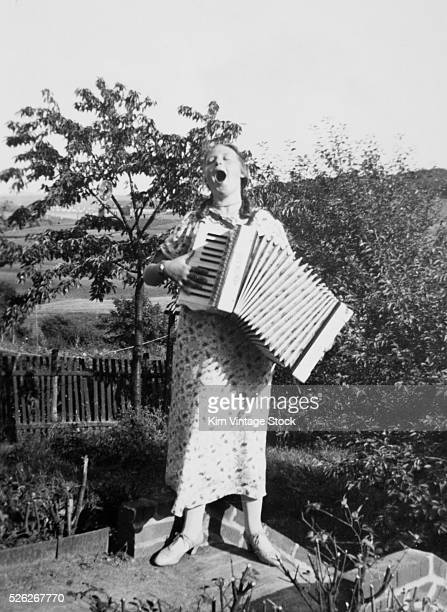 A woman belts out a tune while playing an accordion
