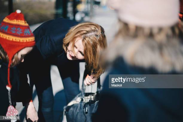 Woman bending and looking at daughter in city on sunny day