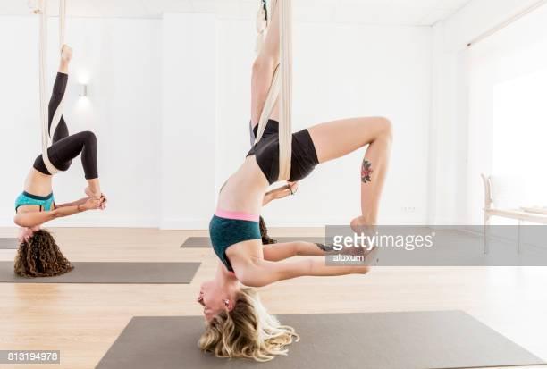 Woman bending backwards during aerial yoga exercises