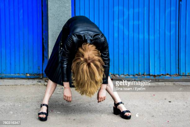 woman bending over against blue corrugated iron wall - bending over stock pictures, royalty-free photos & images