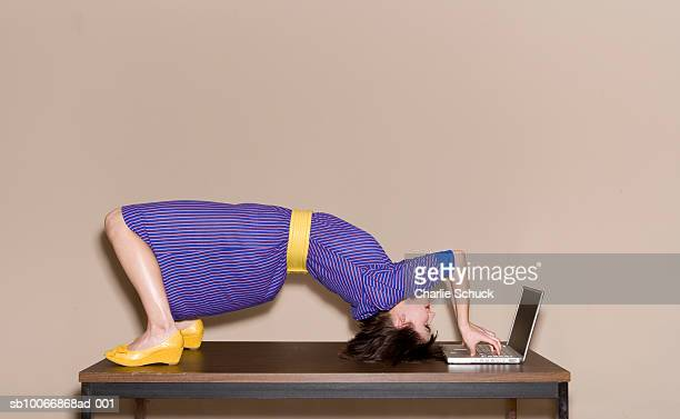Woman bending over backwards on table while working on laptop