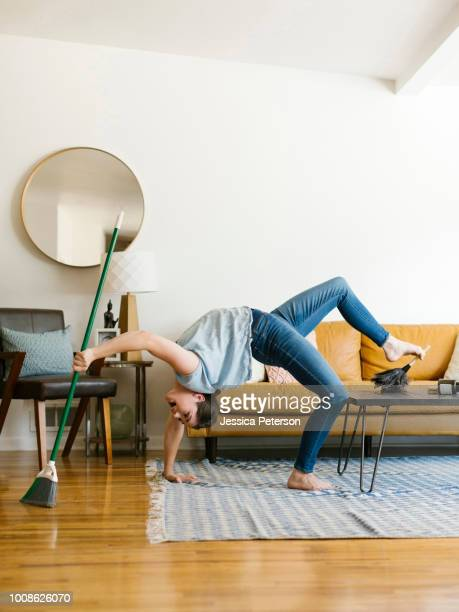 woman bending over backwards sweeping and dusting - standing on one leg stock pictures, royalty-free photos & images