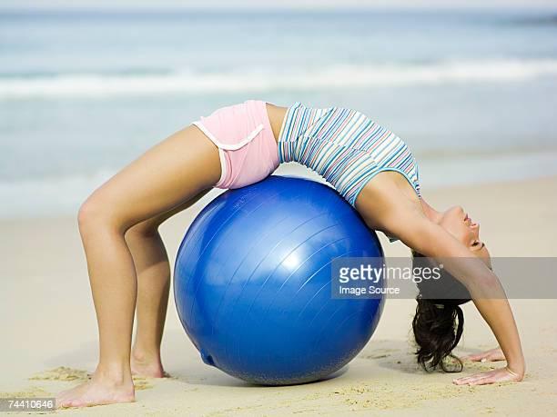 Woman bending over exercise ball