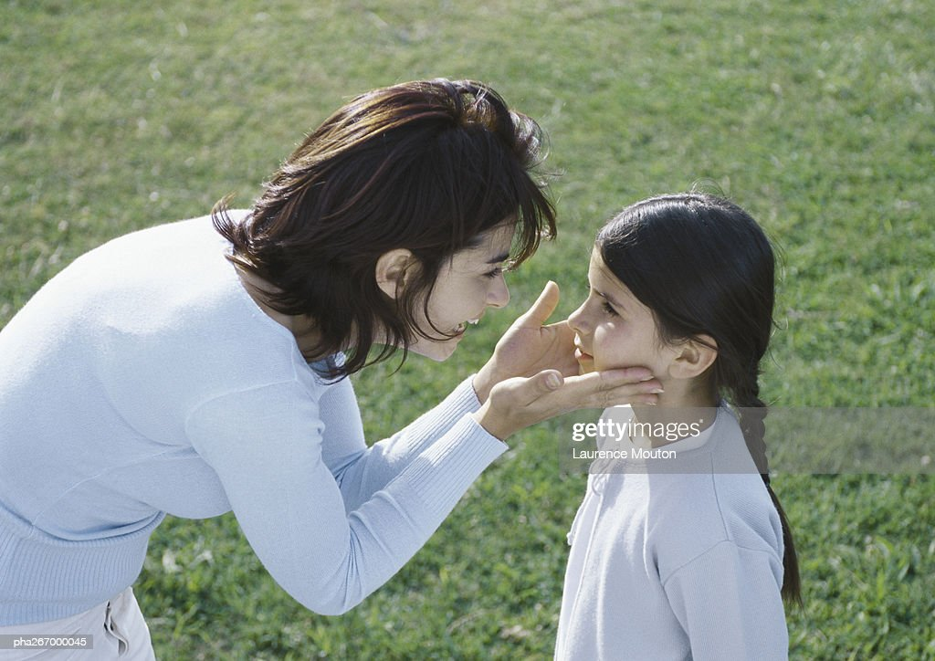 Woman bending over holding daughters face between hands, side view : Stockfoto