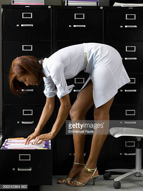 Woman bending over, searching for file, side view
