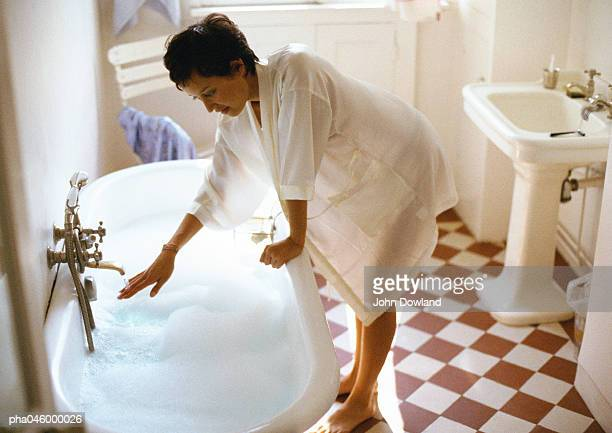 Woman bending over side of bathtub, hand under tap