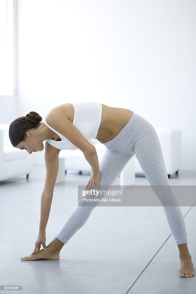 Woman bending over, touching toes : Stock Photo