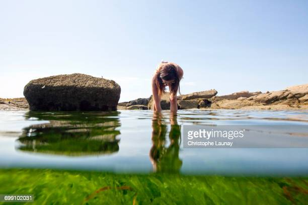 Woman Bending To Take Something Into The Water
