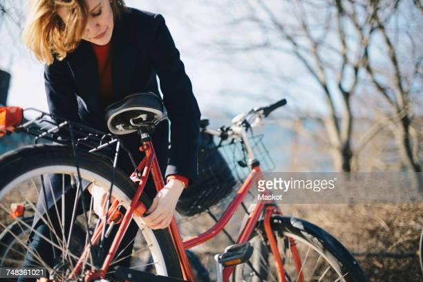 woman bending while locking bicycle on sunny day during winter - unlocking stock pictures, royalty-free photos & images