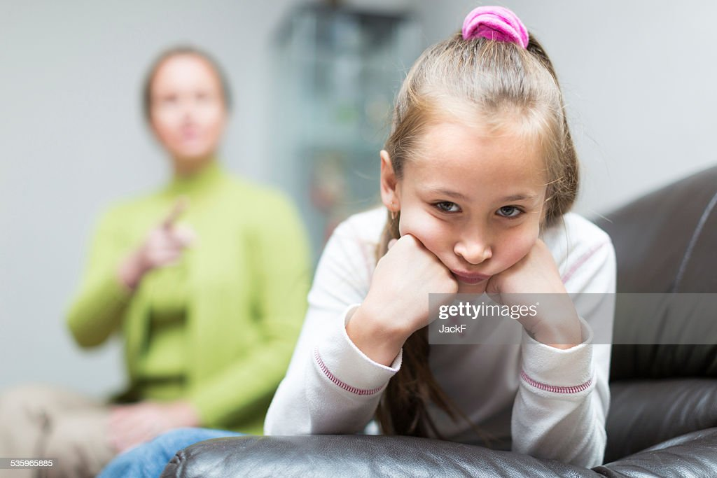 Woman berating daughter in home : Stock Photo