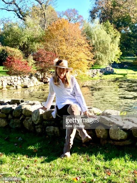 woman beside a lake in autumn - ブーツイン ストックフォトと画像
