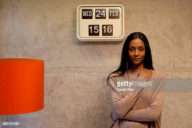 Woman beside flip clock looking at camera smiling