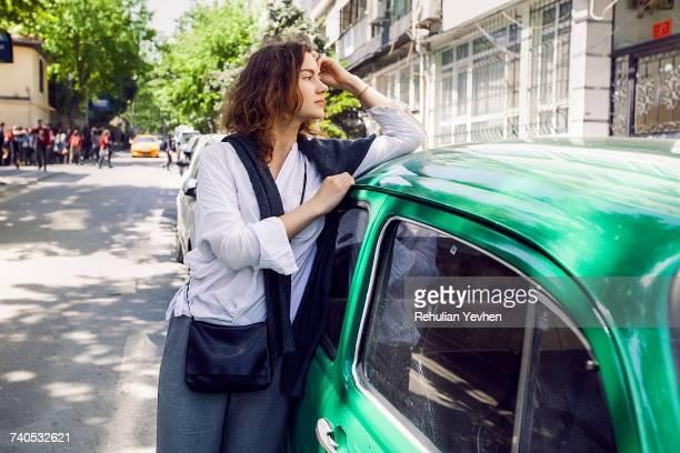 woman beside green car - 近く ストックフォトと画像