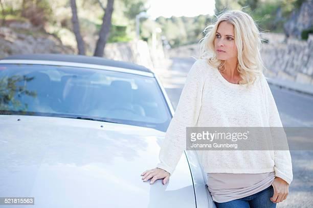 Woman beside her convertible car