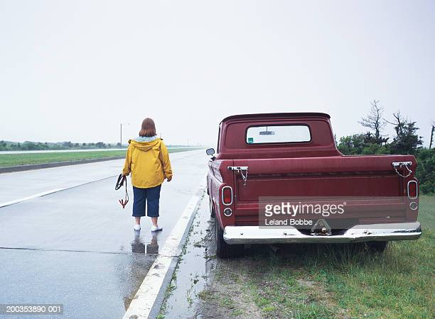 Woman beside truck holding jumper cables, rear view