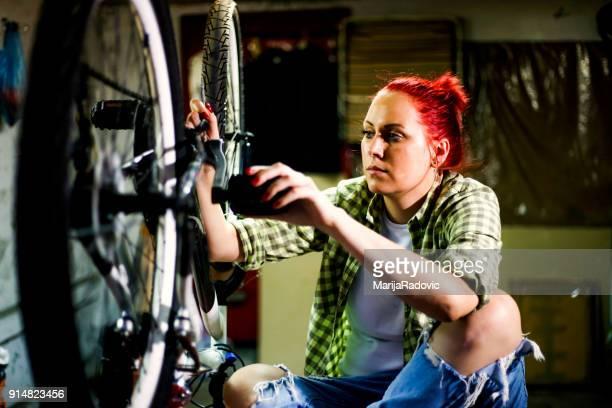 Woman bicycle mechanic is repairing a bike in the workshop