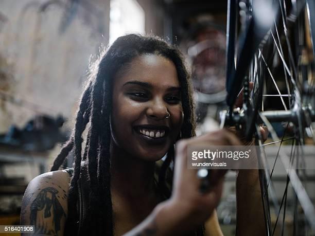 Woman bicycle mechanic with dreadlocks working in bike repair wo