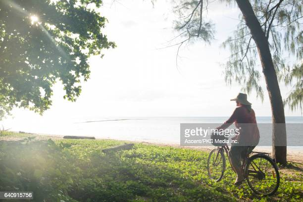 Woman bicycles through green forest, above sea