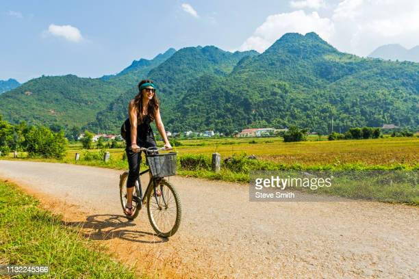 woman bicycling in mai chau, vietnam - mai chau stock pictures, royalty-free photos & images