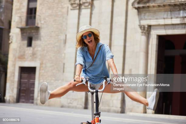woman bike riding on street in barcelona - benen gespreid stockfoto's en -beelden