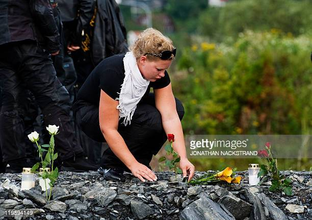 A woman bikers lays flowers and candles on July 26 2011 on the coast of lake Tyrifjorden as she drives through the villages near the Utoeya island in...