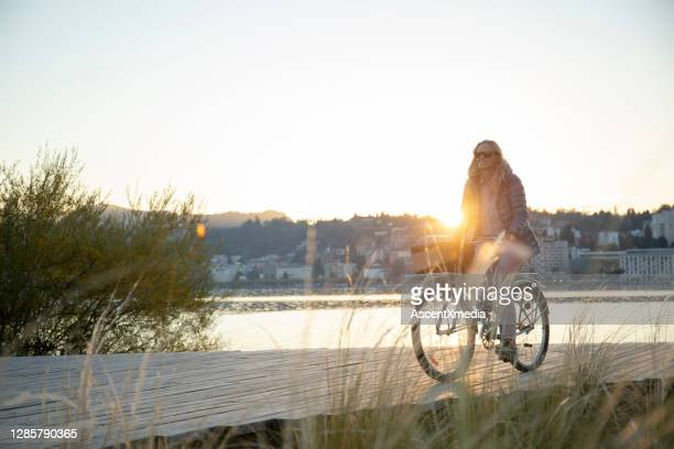 女性は日の出に木製の湖の桟橋を自転車で降りる - スイス ルガーノ ストックフォトと画像