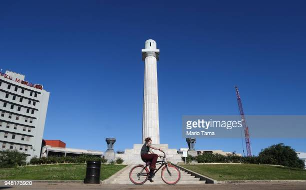 A woman bikes past the pedestal which held Confederate General Robert E Lee's statue which was removed in 2017 amidst controversy on April 17 2018 in...