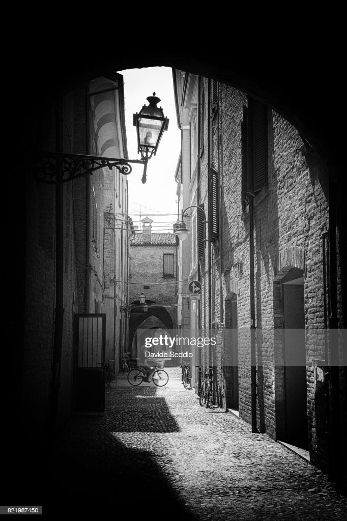 Woman biking in the alleys of the old town : Stock Photo