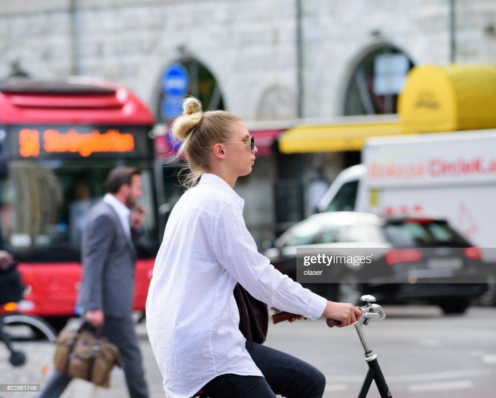 Woman biking in traffic : Stock Photo