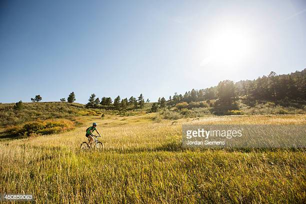 Woman biking on a dirt path.